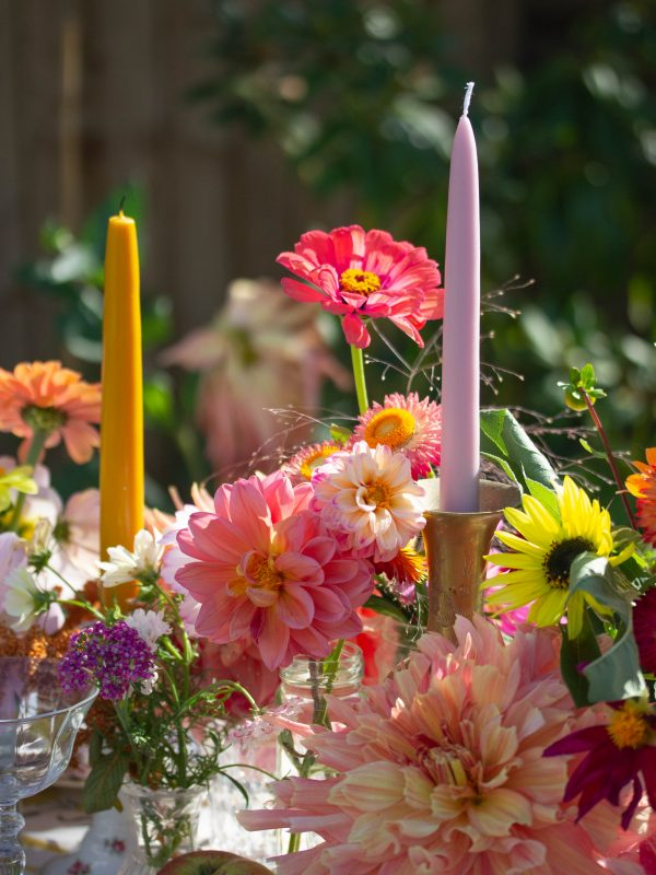Lilac candle and colourful flowers