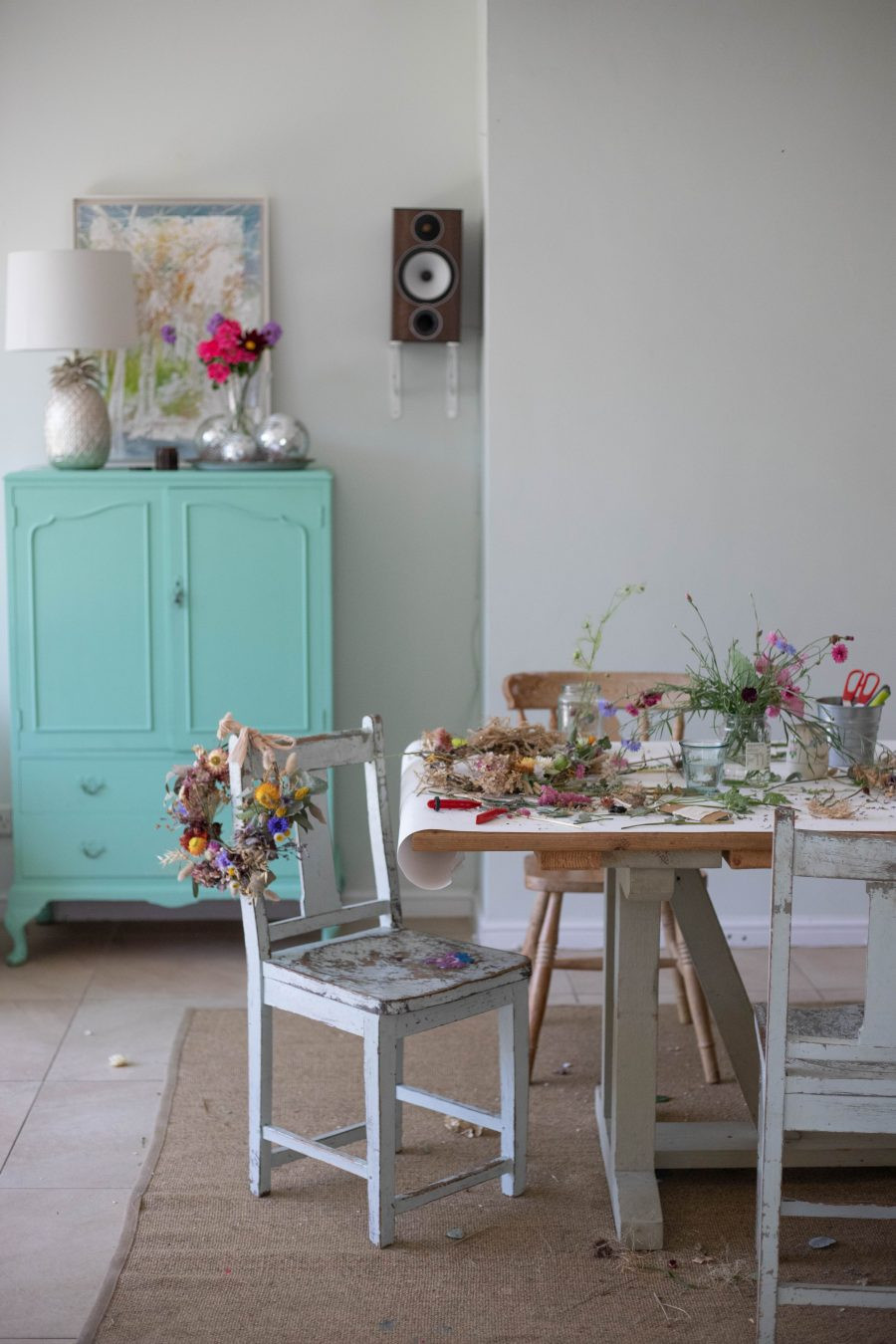 a busy table at the end of a dried flower workshop